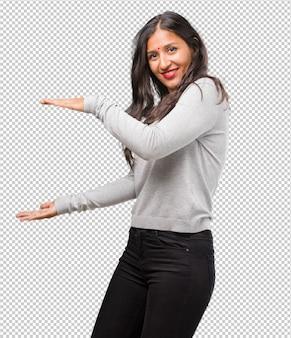 Ritratto di giovane donna indiana tenendo qualcosa con le mani, mostrando un prodotto