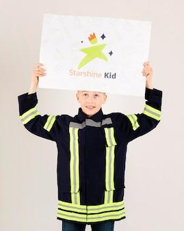Ritratto di giovane ragazzo che posa come vigile del fuoco