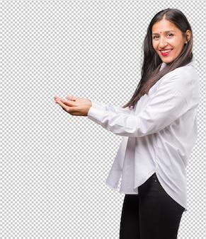 Ritratto di una giovane donna indiana in possesso di qualcosa con le mani, mostrando un prodotto, sorridente e allegro, offrendo un oggetto immaginario