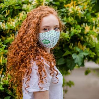 Rode haarvrouw met medisch beschermend gezichtsmasker