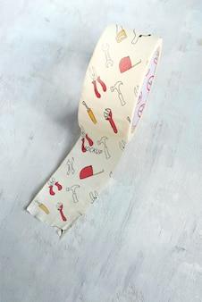 Rollo de cinta adhesiva de papel sobre un fondo de mármol.