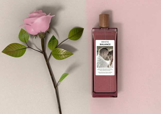 Rosa accanto alla bottiglia di profumo