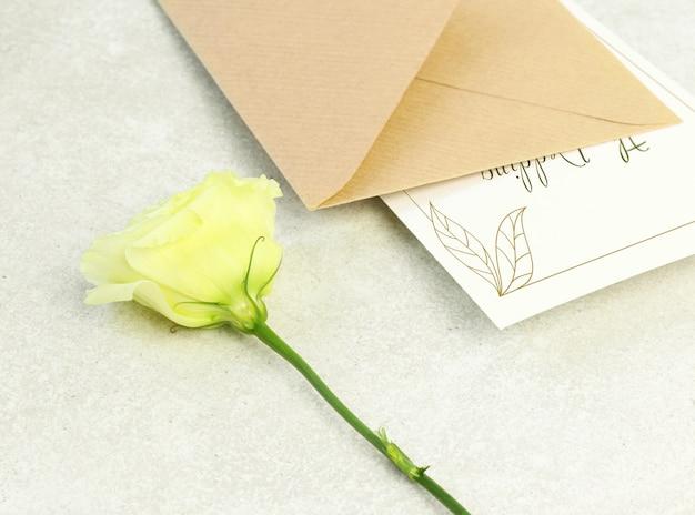 Rosa, sobre y tarjeta de invitación.