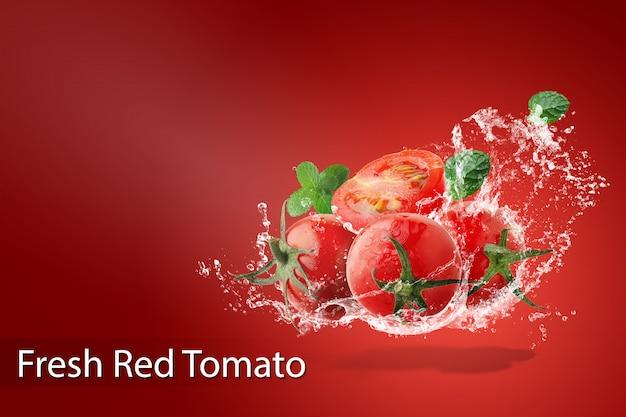 Salpicaduras de agua sobre tomates rojos frescos sobre fondo rojo.