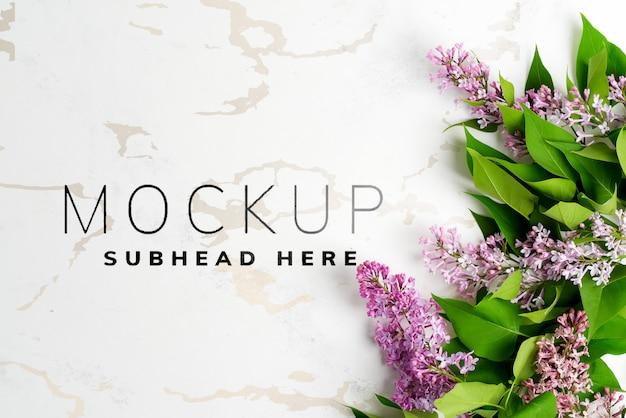 Saludo marco de flores frescas de color lilas con hojas verdes sobre un fondo de mármol gris claro. vista superior.