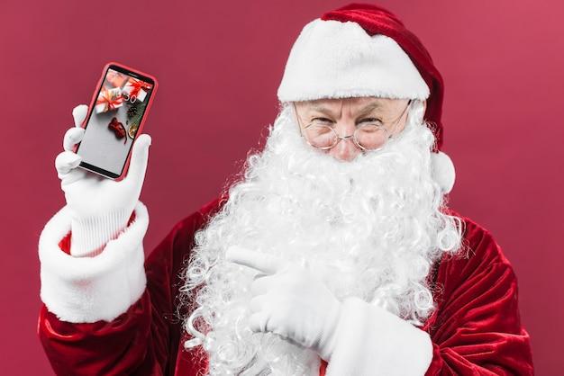 Santa che presenta il mockup di smartphone