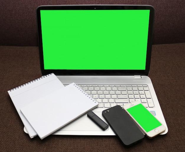Schermo del computer portatile verde e smartphone con il blocco note a spirale e flash drive
