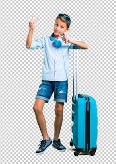Scherzi con gli occhiali da sole e le cuffie che viaggiano con la sua valigia che sorride e che mostra il segno di vittoria