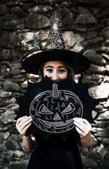 Schets van een gesneden pompoen en een vrouw gekleed als een heks
