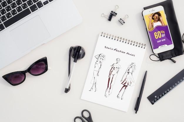 Schizzo di moda sulla scrivania con strumenti accanto