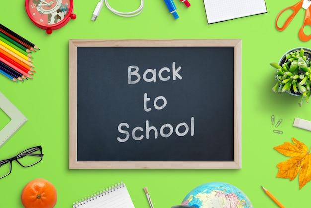 Schoolbordmodel met krijtteksteffect omringd door schoolbenodigdheden. bovenaanzicht scène maker met gescheiden lagen op groen bureau