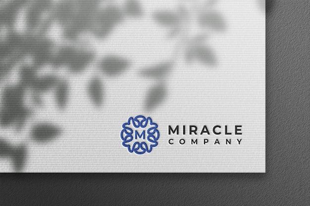 Schoon logo-mockup in wit geperst papier met plantenschaduw