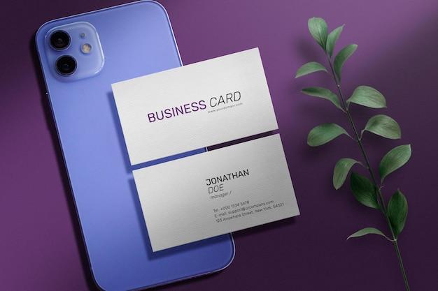 Schoon minimaal visitekaartje mockup op paarse mobiel met klein blad