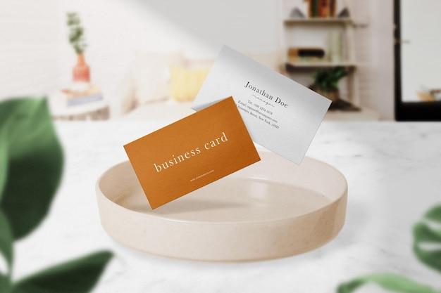 Schoon minimaal visitekaartjemodel dat op een bord in een kamer drijft