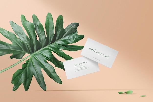 Schoon minimaal visitekaartjemodel drijvend op een gekleurde achtergrond met blad.