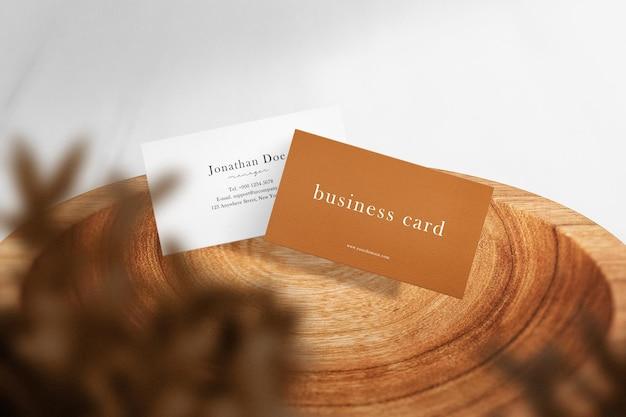 Schoon minimaal visitekaartjemodel drijvend op een houten bord met bladeren