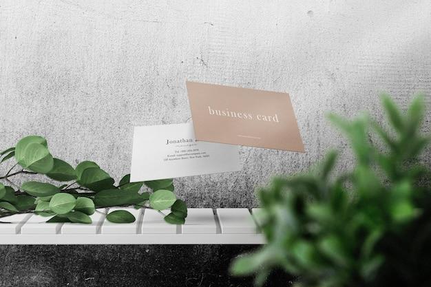 Schoon minimaal visitekaartjemodel drijvend op een witte plank met bladeren