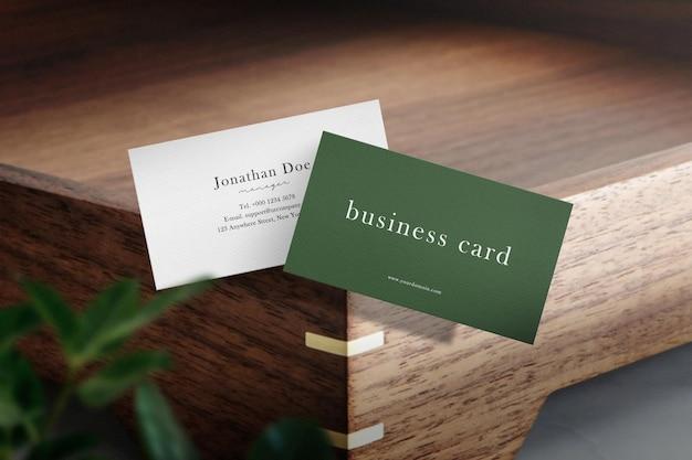 Schoon minimaal visitekaartjemodel drijvend op houten plaat met bladeren.