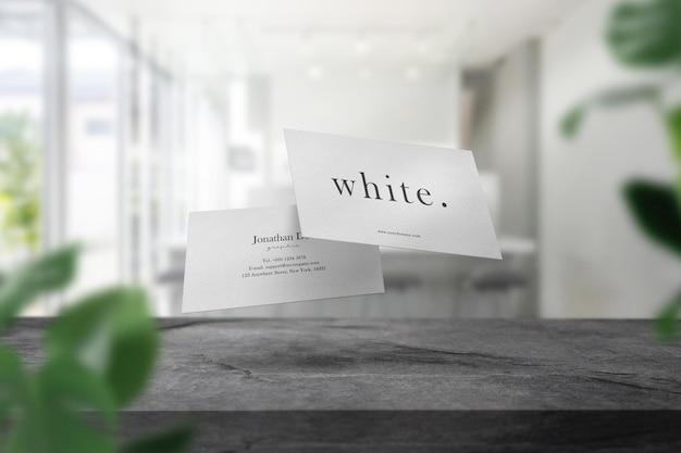 Schoon minimaal visitekaartjemodel op bovenste tafel op witte caféachtergrond.