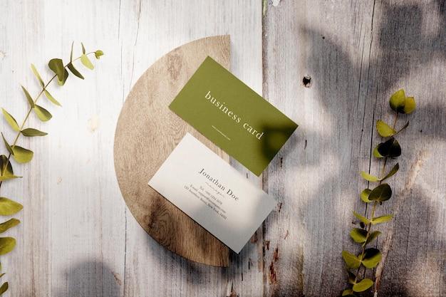 Schoon minimaal visitekaartjemodel op houten bord met bladeren