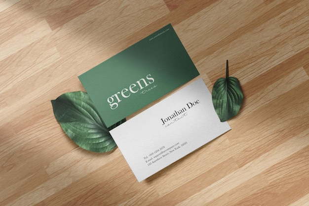 Schoon minimaal visitekaartjemodel op houten vloer met groene bladeren