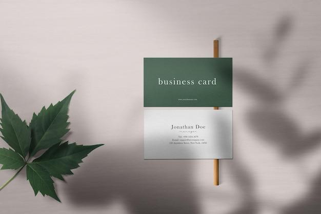 Schoon minimaal visitekaartjemodel op houtstructuur met blad.