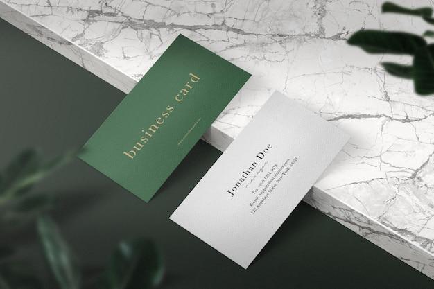 Schoon minimaal visitekaartjemodel op marmeren bord met bladeren