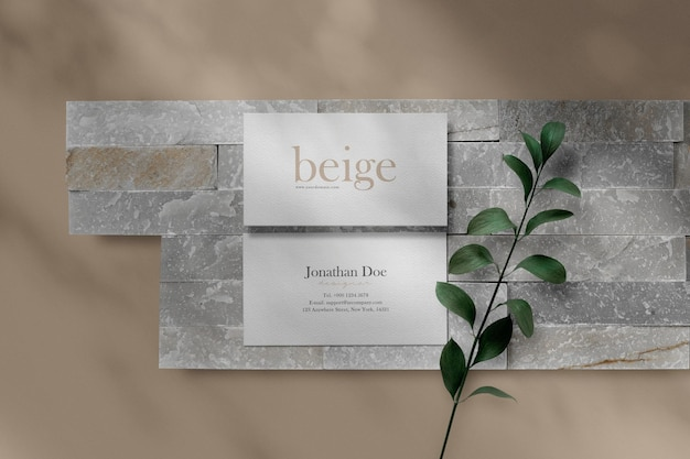 Schoon minimaal visitekaartjemodel op steenplaten met kleine bladerenachtergrond.