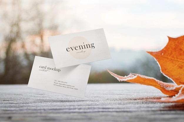 Schoon minimaal visitekaartjemodel op tafel met esdoornbladachtergrond.