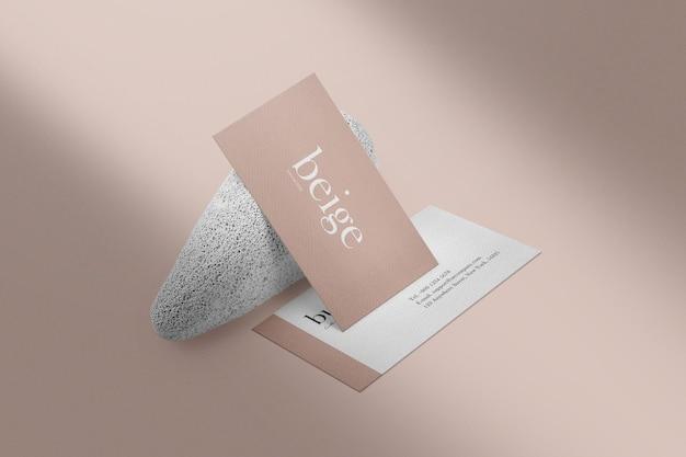 Schoon minimaal visitekaartjemodel op witte steenachtergrond.