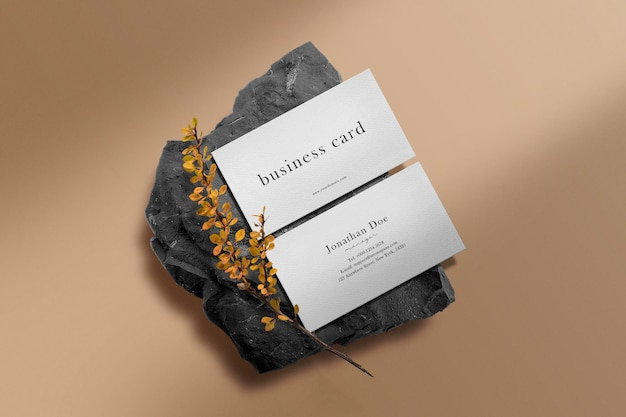 Schoon minimaal visitekaartjemodel op zwarte steen met gele plant