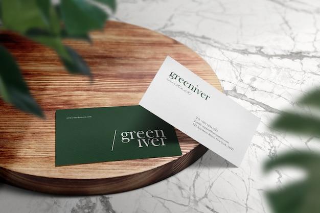 Schoon minimaal visitekaartjesmodel op houten cirkeltafel en groene bladerenschaduw.