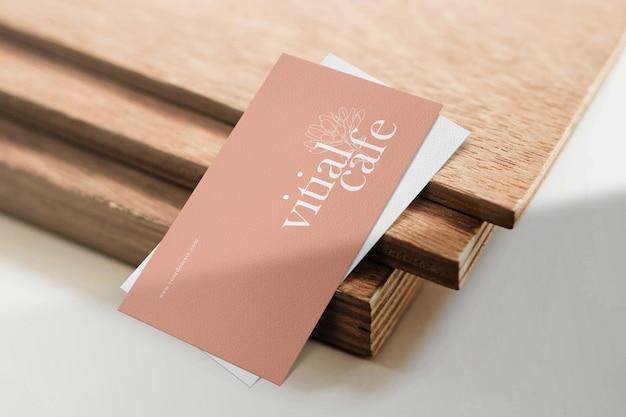 Schoon minimaal visitekaartjesmodel op houtplaat met lichte schaduw.