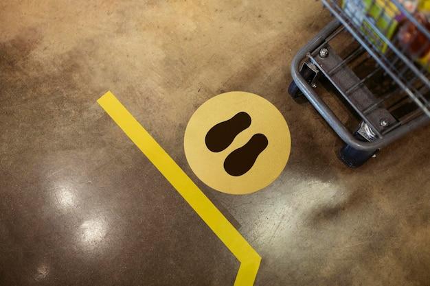 Señal de distanciamiento social de supermercados en el suelo durante la pandemia de coronavirus