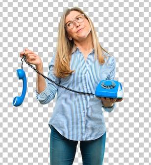 Senior bella donna con un telefono vintage