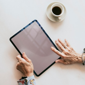 Senior vrouw die een digitaal tabletmodel gebruikt