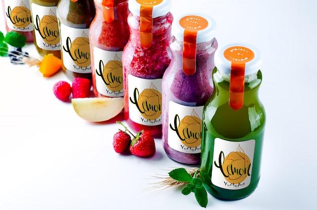 Set con color smothie in bottiglie di vetro con copia spazio su bianco
