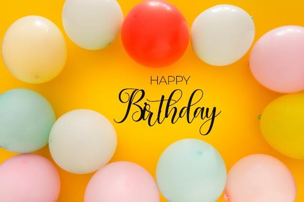 Sfondo di compleanno con palloncini colorati su giallo