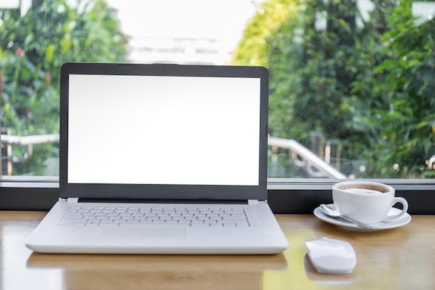 Simulacros de pantalla en blanco de la computadora portátil con una taza de café en la mesa de madera con trazado de recorte fondo borroso.