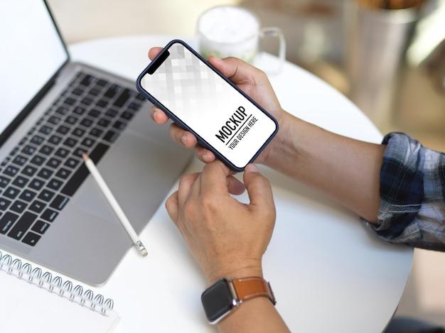 Sluit omhoog van zakenmanhanden die smartphonemodel gebruiken