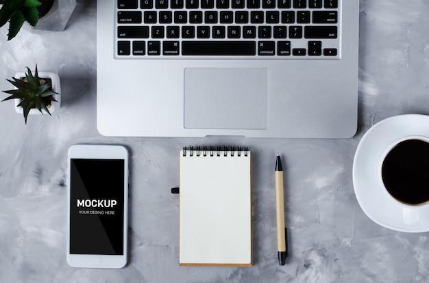 Smartphone blanco con pantalla en blanco negro en escritorio de oficina con laptop y taza de café