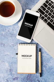 Smartphone blanco con pantalla en blanco negro en el escritorio de oficina con ordenador portátil, cuaderno vacío y taza de té