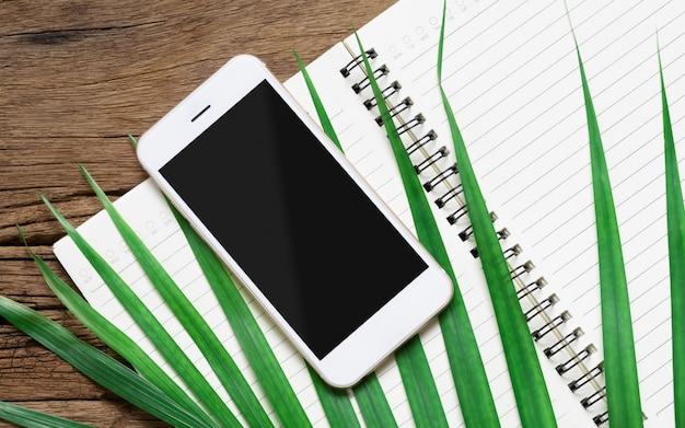Smartphone blanco con pantalla de maqueta en blanco negro con hojas de palma verdes y cuaderno abierto
