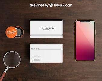 Smartphone e maquete de crachá com pilhas de cartões de visita