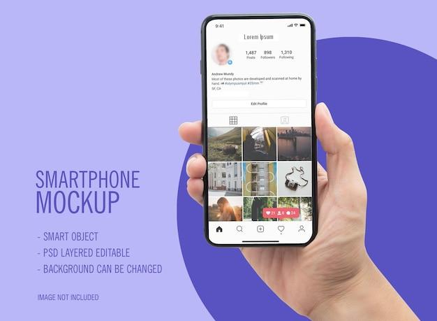 Smartphone en mano con maqueta de instagram