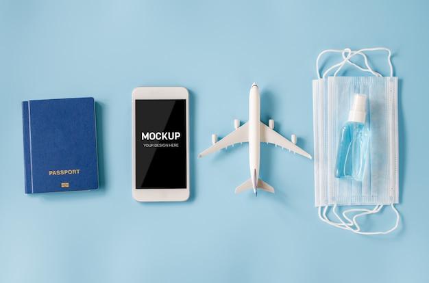 Smartphone met vliegtuigmodel, paspoorten, gezichtsmasker en ontsmettingsmiddel