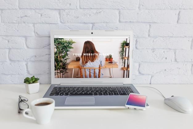 Smartphone-model met laptop en werkruimteconcept