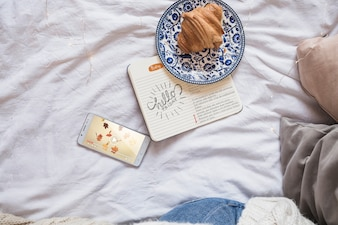 Smartphone na cama com diário e croissant
