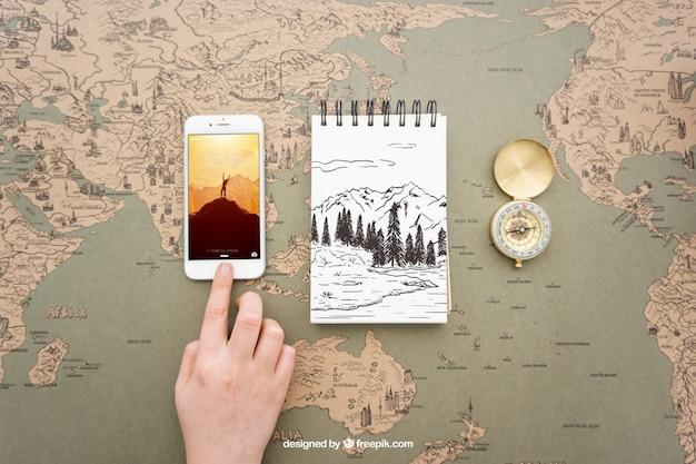 Smartphone, notitieblok en kompas op kaart van de wereld