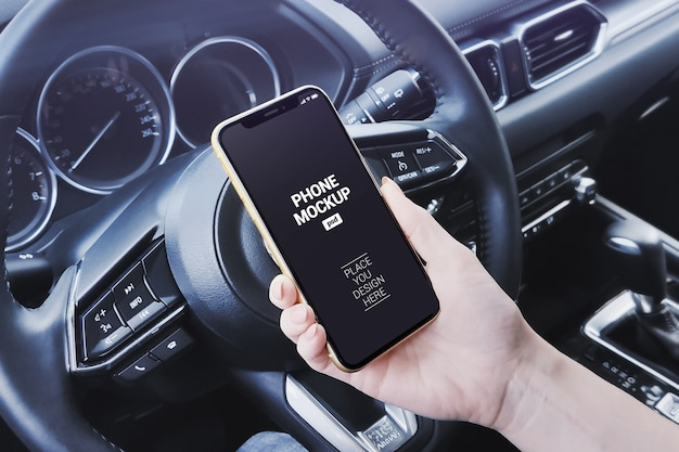 Smartphone van de handholding in het model van de autoscène